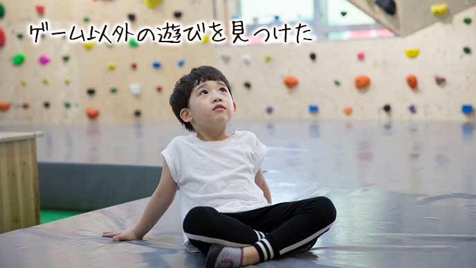 ボルダリングの壁を見上げる子供