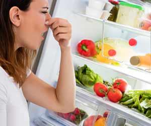 冷蔵庫の中を見ながら鼻を摘まむ女性