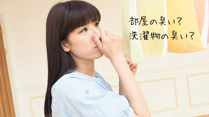 室内で干すタオルの前で鼻を摘まむ女性