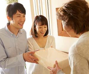 玄関で親戚に挨拶する夫婦