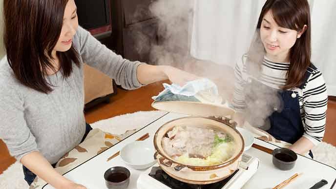 こたつで鍋料理を食べる女性達