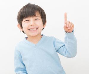 人差し指を上げて笑顔の子供