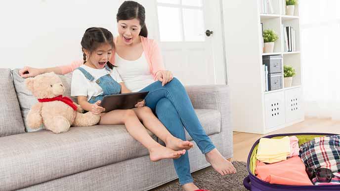 ソファに並んで座りタブレットでスケジュールを見る親子