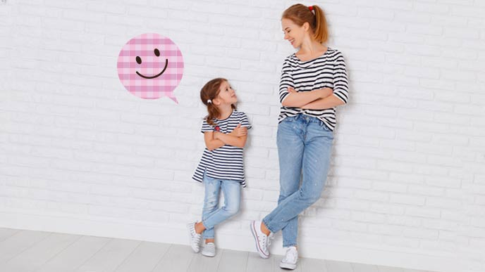親子リンクコーデで笑顔でママを見る子供