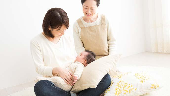 子どもを抱っこする母親と傍で見守る産後ドゥーラ