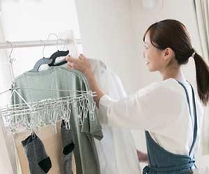 洗濯ものを部屋の中に干す主婦