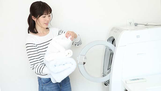 洗濯機から洗濯ものを取り出す主婦