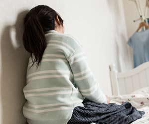 部屋の壁にもたれかかる子供