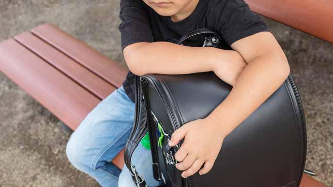 ベンチにランドセルを置いて無言の小学生