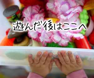 玩具をボックスへ仕舞う子供の手