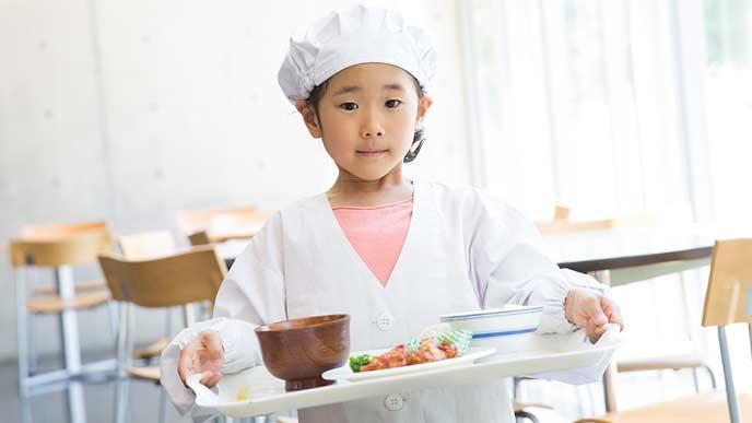 白衣を着て配膳する小学生