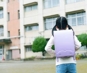 学校を前にして立ち止まる小学生