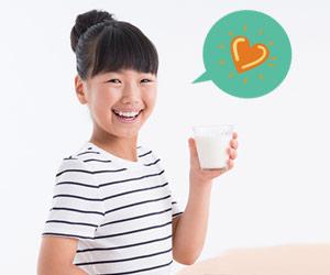 朝食のミルクを飲む小学生