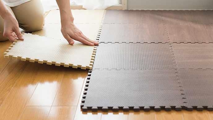 ジョイントマットを床に敷く主婦