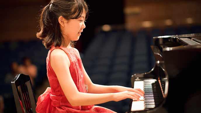 ピアノコンクールでドレスを着てピアノを弾く女の子