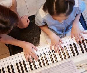 ピアノ教室で先生に教えてもらう子供