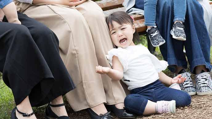 足元で泣く子供を放置する母親
