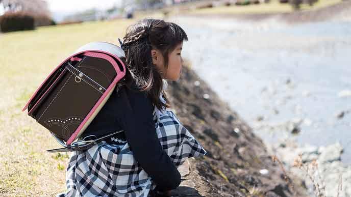 一人で川を見つめる小学一年生