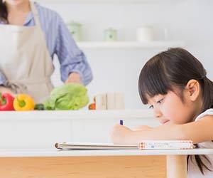 調理する母親の傍で勉強する子供