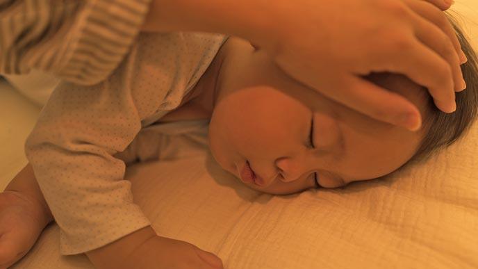 眠る赤ちゃんの様子を見る母親