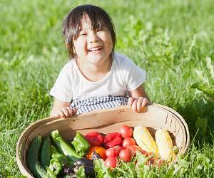入学前の幼児が笑顔で採れたての野菜を見せる