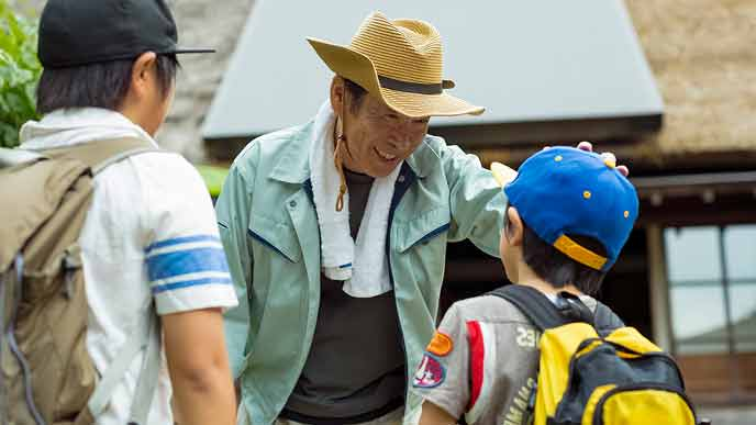 山村留学の子供を笑顔で迎える田舎の年配男性
