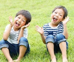 芝生に並んで座る双子の男の子