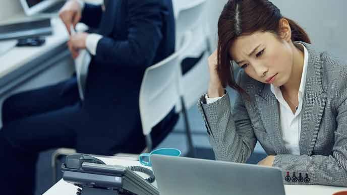 困惑した表情で会社のデスクに座る女性