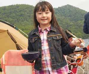 テントの前で食器と箸を持つ子供