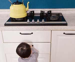台所のガスコンロの下で遊ぶ幼児