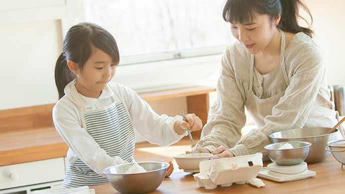 母親とお菓子作りをする女の子
