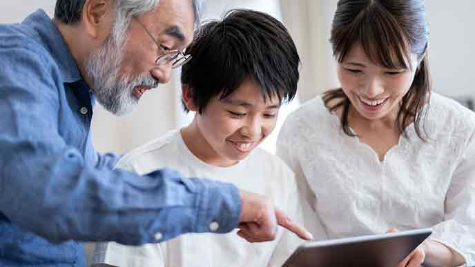 孫と娘とおじいちゃんがタブレットを見る