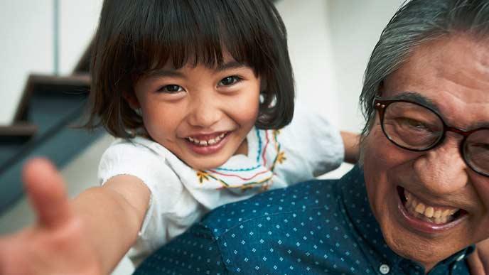 おじいちゃんの背中で遊ぶ女の子