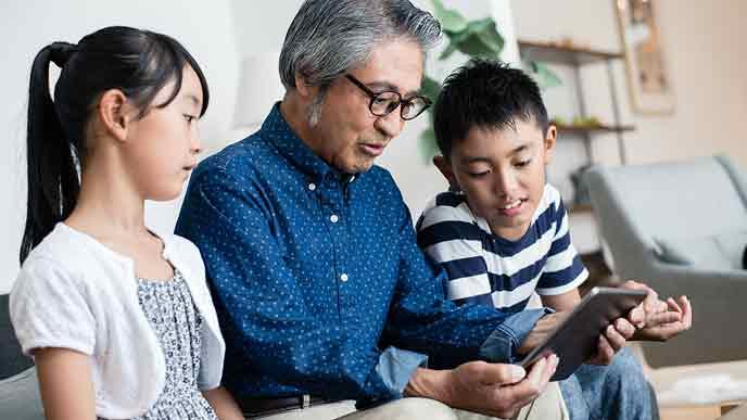 孫とタブレットを見るおじいちゃん