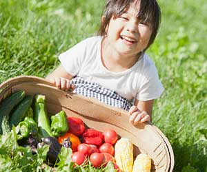 もらった野菜を見せる子供
