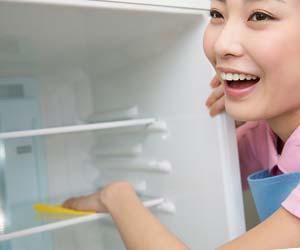 冷蔵庫の中を拭く女性