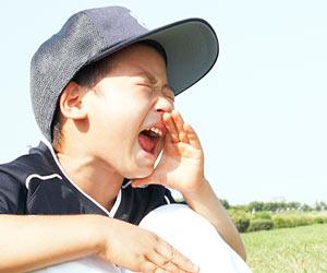 野球チームの仲間を応援する子供