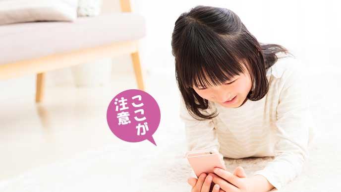 自宅でスマホを見る小学生の女の子