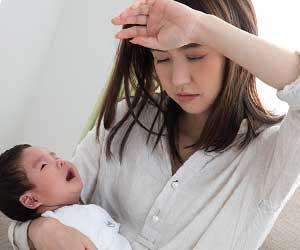 赤ちゃんを抱っこしながら疲労の色を見せる母親