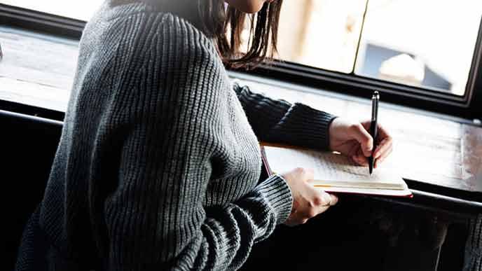 ノートへ書き込む女性