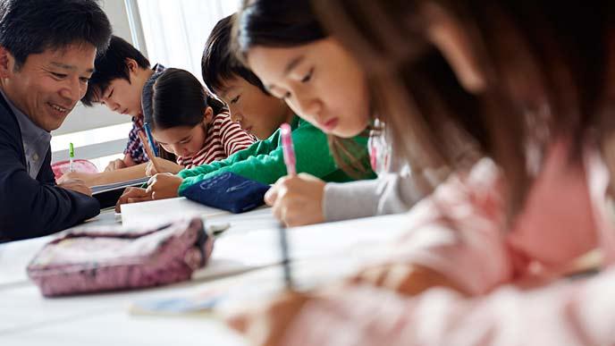 勉強する子供達と先生