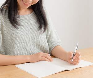 交換日記に書き込む母親