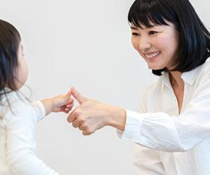 幼児と親指を合わせる母親
