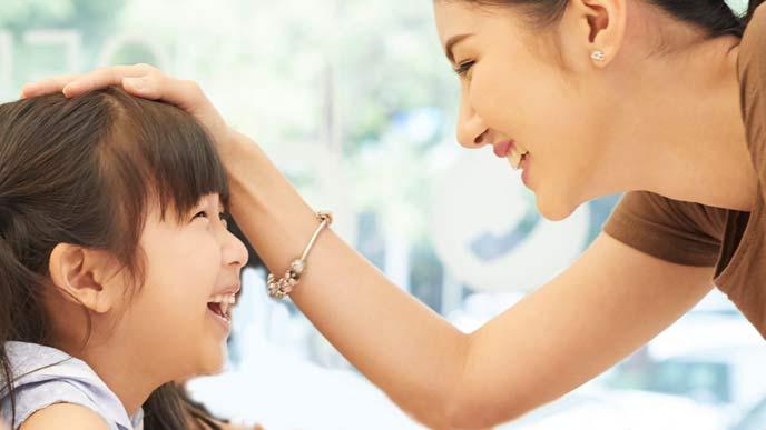 子供の頭を撫でて褒める母親