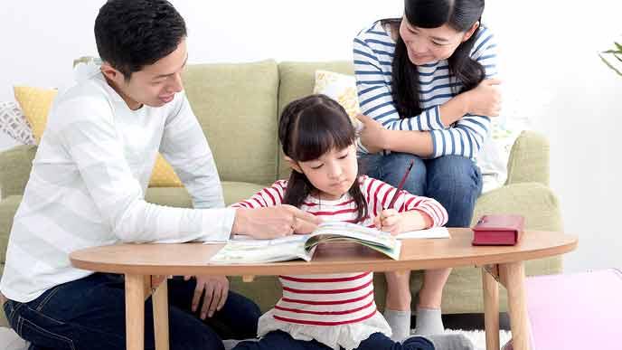 親に教えてもらいながらリビングで勉強する小学生