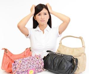色々なショルダーバッグを前にして迷う女性