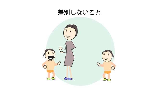 双子の一人と話す母親と離れて見つめる片方の子