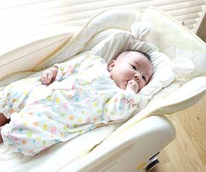 ハイローチェアに寝かせられた赤ちゃん