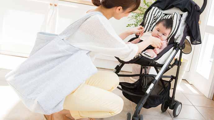 トートバッグを肩にかけて赤ちゃんをベビーカーに乗せる女性