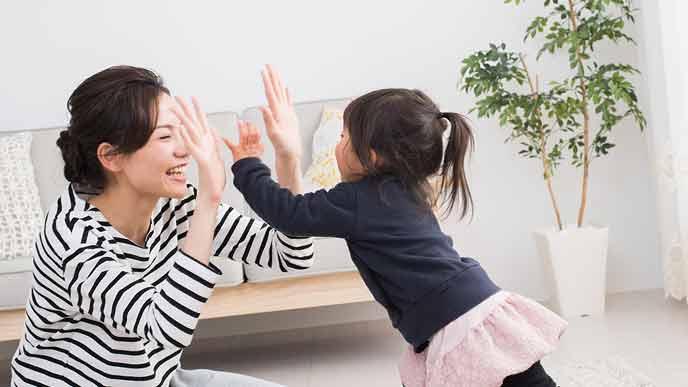 子供と手のひらを合わせて笑う母親